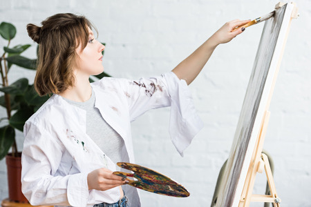 Young creative girl smears paint on canvas in light studio Stock Photo
