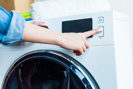 close-up partial view of woman using washing machine at home 写真素材