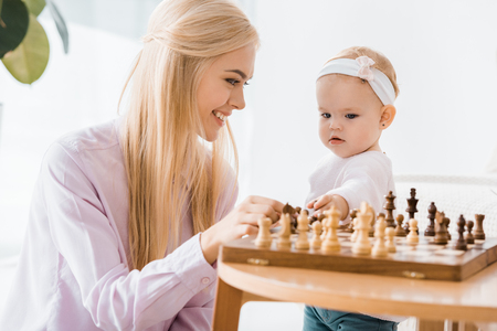 young cheerful mother teaching daughter playing chess Imagens