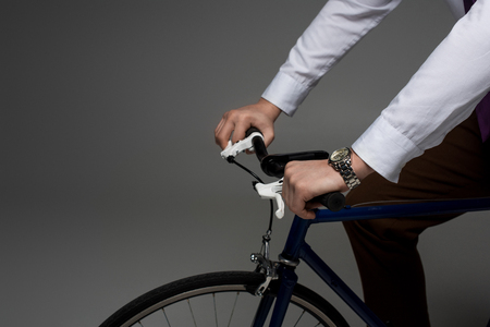 Partial view of businessman riding on bicycle isolated on grey Stok Fotoğraf