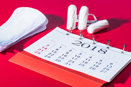 tampons, daily pads and calendar on red 版權商用圖片