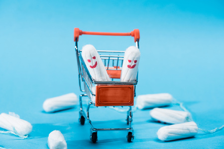 tampons with happy smileys in small shopping cart on blue Zdjęcie Seryjne