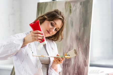 Young creative girl squeezing paint tube in light studio