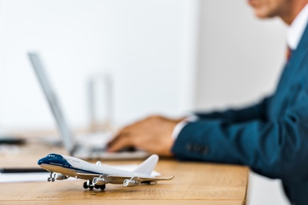 toy airplane at wooden table with office worker using laptop on blurred background Stockfoto