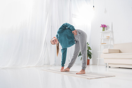 girl stretching on yoga mat at home