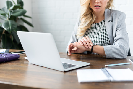 cropped image of businesswoman looking at watch on office with laptop Stock Photo