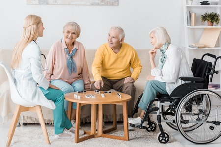 young female nurse playing domino with senior patients Standard-Bild