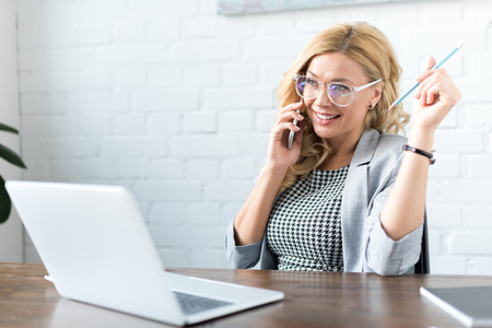 happy businesswoman talking by smartphone in office with laptop