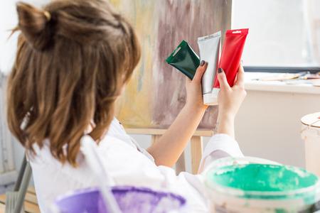 Young inspired girl choosing paint tube in light studio Stok Fotoğraf