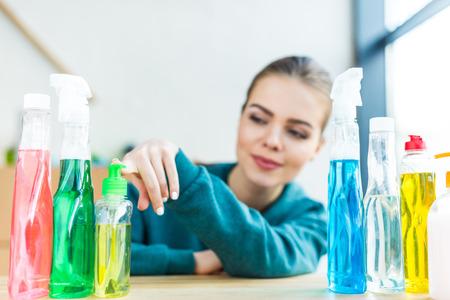 Mujer sonriente mirando varias botellas de plástico con productos de limpieza