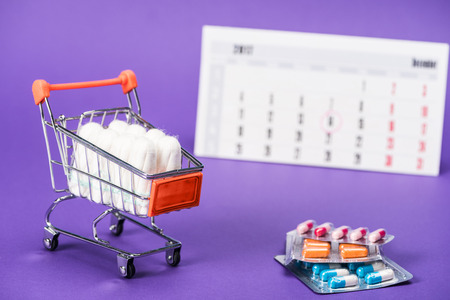 tampons in small shopping cart, pills and calendar on purple Stock fotó