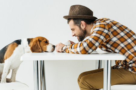 side view of man touching dog nose at table