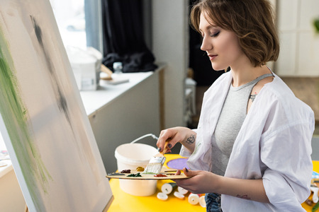 Young inspired girl mixing paint in light studio