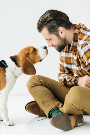side view of dog sniffing man nose Stock Photo