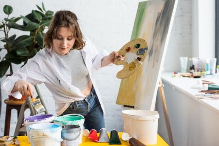 Young artistic girl choosing paint in light studio