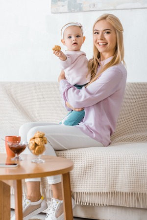 young woman sitting on sofa with small daughter holding cookie Stock Photo