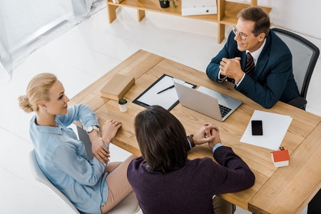 adult insurance agent in glasses talking to young couple in office Banco de Imagens