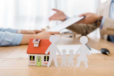 White paper cut family and house model on wooden table with blurred people at background, life and house insurance
