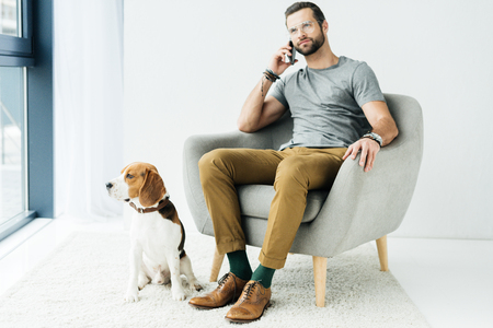 man sitting on armchair and talking by smartphone, dog sitting near