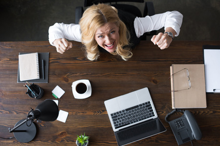 overhead view of businesswoman screaming and showing yes gesture in office Stock Photo