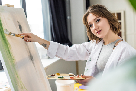 Young creative girl painting in light studio Stock Photo