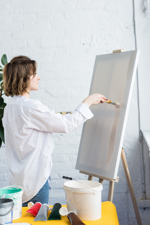 Young creative girl applying artistic primer in light studio Stock Photo