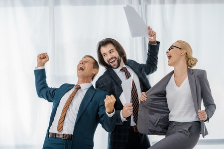 happy office workers rejoicing great deal in office Stock Photo