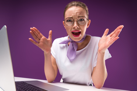 shocked girl gesturing with hands and looking at camera isolated on purple