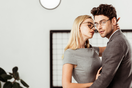 Side view of businesswoman hugging colleague that looking at camera in office, office romance concept