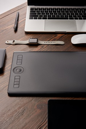 Close-up shot of professional graphics tablet with various gadgets on wooden table Stock Photo