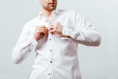 Partial view of businessman buttoning up white shirt isolated on grey