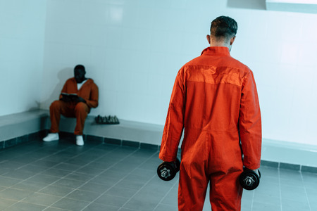 Rear view of prisoner training with dumbbells in prison cell Stock Photo