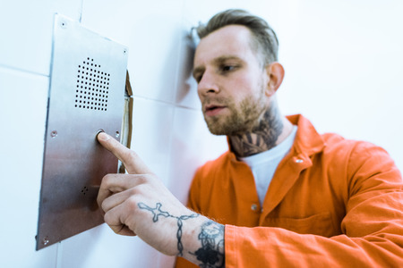 Tattooed criminal in orange uniform pressing button in prison cell Banco de Imagens