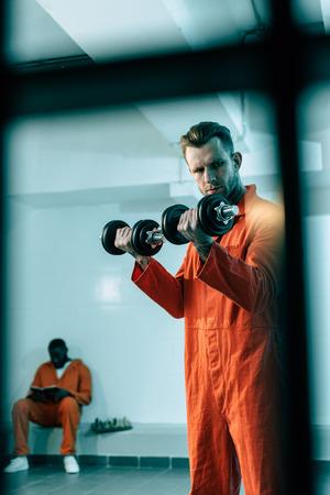 Prisoner training with dumbbells in prison room behind prison bars