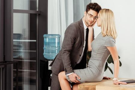Seitenansicht von Geschäftskollegen, die am Arbeitsplatz im Büro flirten, Büroromantikkonzept