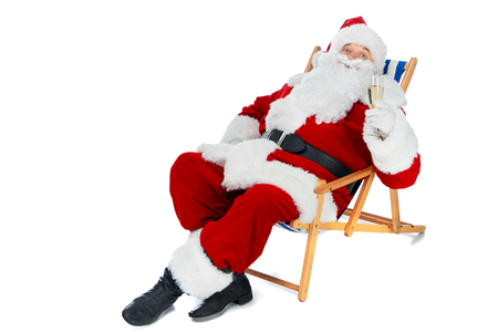 Santa Claus resting on beach chair with champagne glass isolated on white Stock Photo