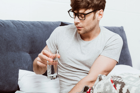 Selective focus of young man in eyeglasses drinking water in bed at home Stock fotó