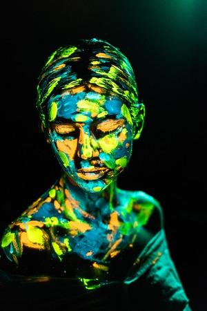 Portrait of woman painted with bright neon paints on black backdrop Foto de archivo - 112272991