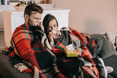 Sick young couple with paper napkins sneezing while sitting on couch under plaid at home