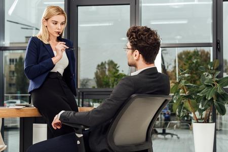 Attraktive Geschäftsfrau flirtet mit Geschäftskollegen am Arbeitsplatz im Büro