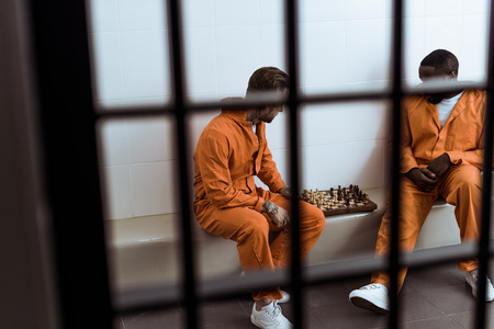 Multiethnic prisoners playing chess behind prison bars
