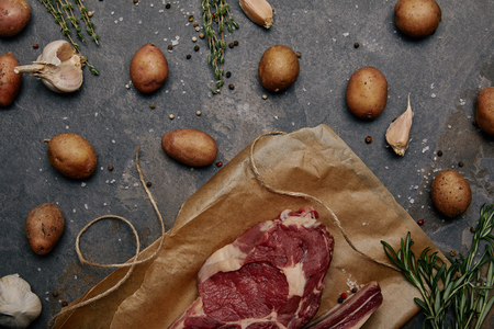 Flat lay with raw meat steak on baking paper with spices and potatoes on grey background
