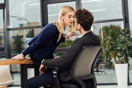 Side view of attractive businesswoman flirting with business colleague at workplace in office