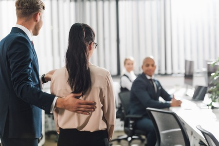 Back view of businessman introducing new colleague to young business people in office