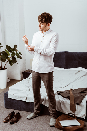 Young handsome businessman buttoning up white shirt in bedroom at home