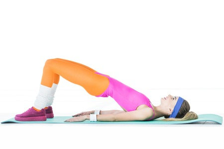 Side view of smiling sporty girl lying and training on yoga mat isolated on white
