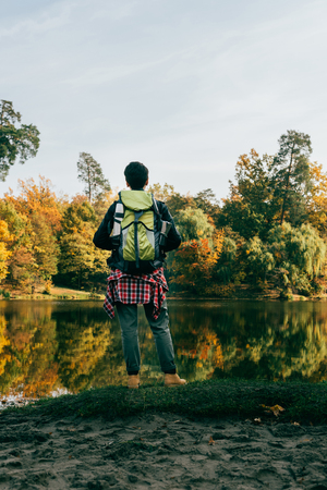 rear view of traveller with backpack on autumnal background Stock Photo