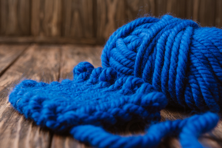 close up view of blue yarn for knitting on wooden surface