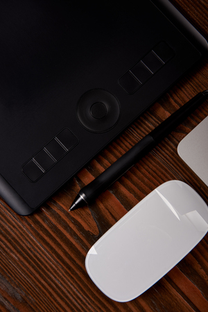 close-up shot of graphics tablet with wireless computer mouse on wooden table