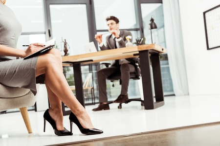 partial view of businesswoman with notebook sitting in armchair with colleague at workplace in office